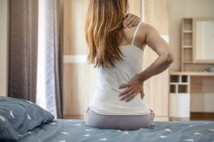 Woman suffering from back ache due to degenerative disc disease on the bed