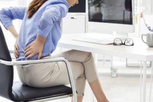 Business woman with back pain sitting in chair in need of decompression therapy