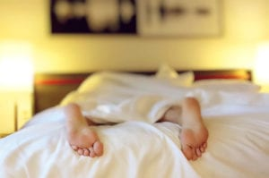 feet hanging off the bed which could cause low back pain from sleeping position on stomach