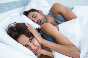 Woman lying in bed with ears covered from husband snoring who needs sleep apnea treatment
