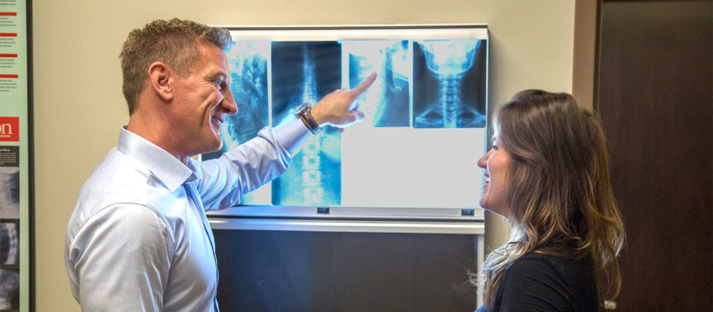 Dr Crist showing a female patient her chiropractic back x-rays