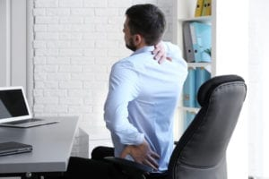 Man hurting from scoliosis pain at computer.
