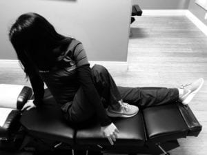 woman seated on chiropractic table with left leg outstretched and right leg pulled up with left arm crossed over right knee facing toward back wall