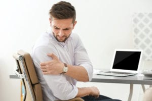 Man sitting at desk in pain due to a pinched nerves in his shoulder