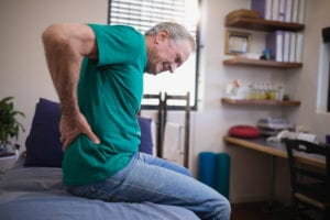 man grabbing his lower back from pain likely caused by piriformis syndrome