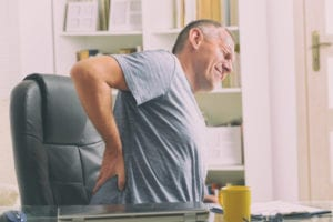 Man grabbing his lower back while sitting at a desk because he needs treatment for degenerative disc disease