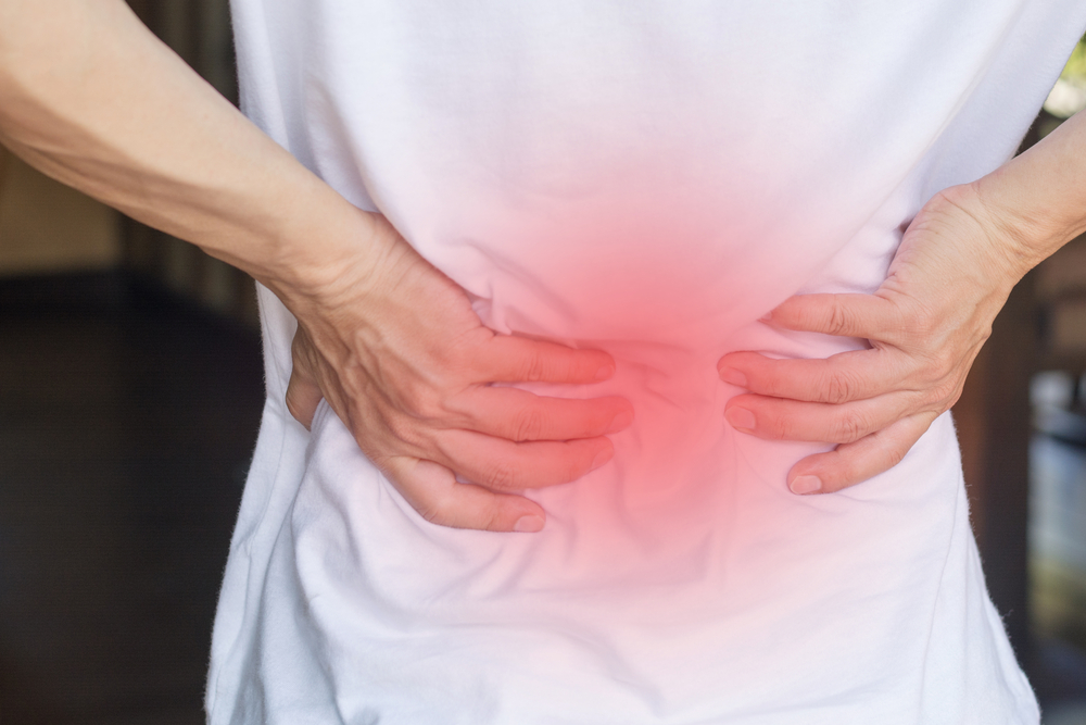 Man's hands on his back with red spot as suffering from sacroiliac pain.