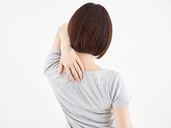 Lady clutching shoulder blade due to pain from a bulged disc in her cervical spine.