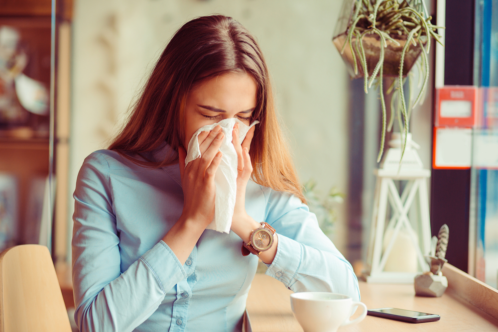Woman blowing nose due to allergies.