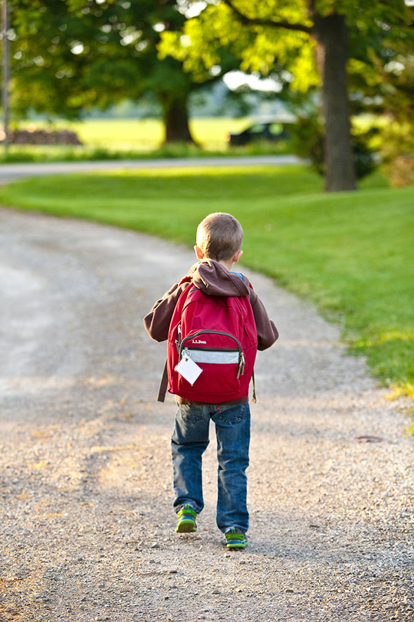 boy walking down street with backpack