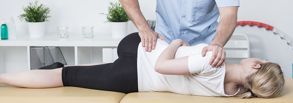 lady on chiropractic table performing exercise with chiropractor's help