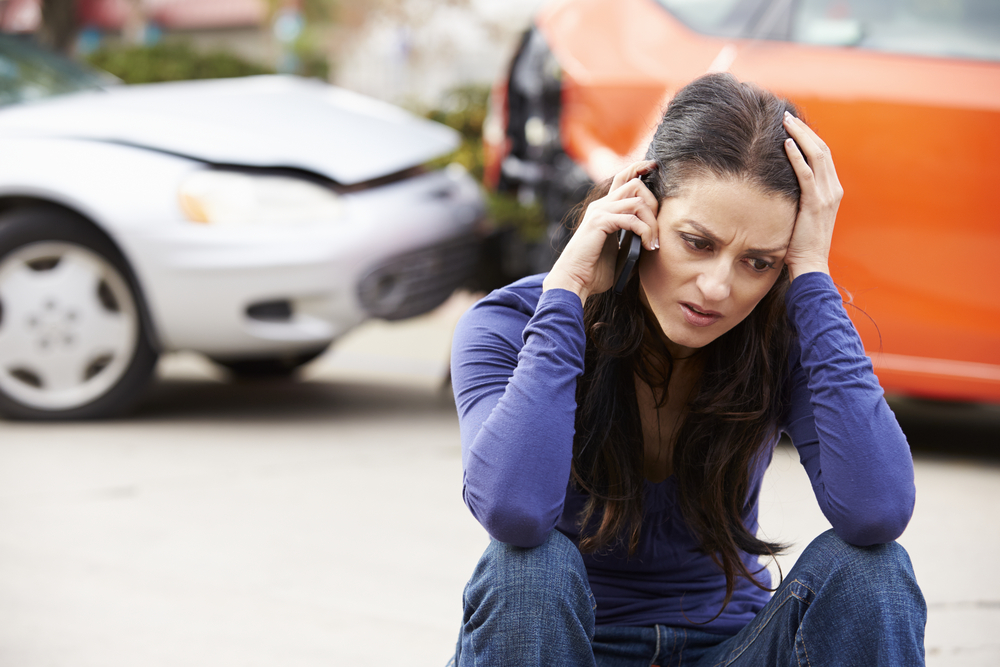 Woman upset on the phone after a car accident.